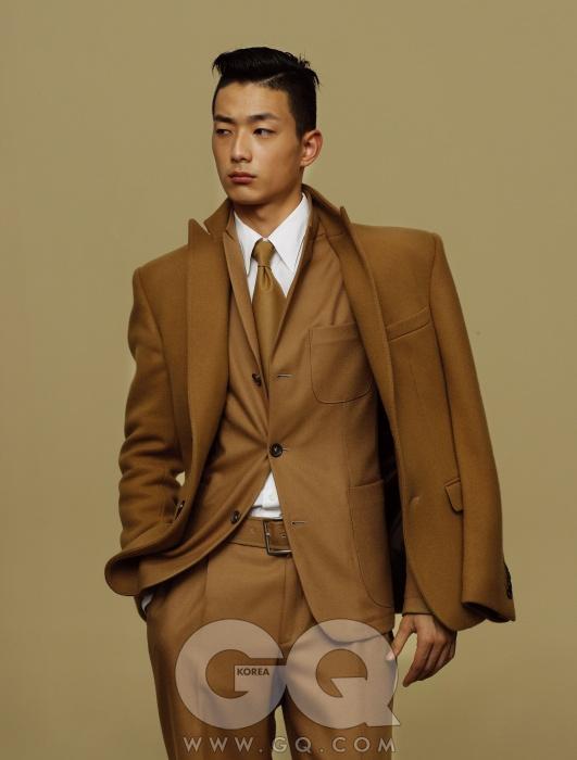 Z Zegna 카멜 수트와 덧입은 진한 갈색 재킷, 화이트 셔츠와 타이, 모두 Z 제냐.