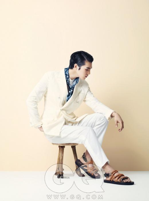 흰색 더블 브레스티드 수트, 흰색 헨리 네크라인 셔츠, 파란색 머플러, 샌들 모두 루이 비통.