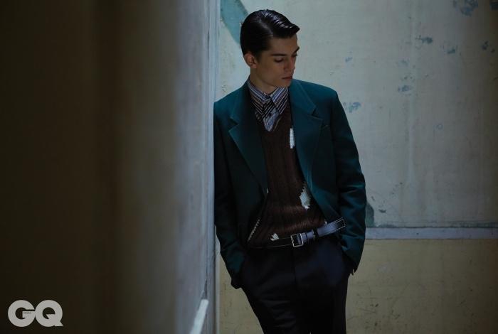 진한 녹색 테일러드재킷, 줄무늬 포플린 셔츠,캐시미어 브이넥 니트, 검정팬츠, 스티치 장식 가죽벨트, 모두 프라다.