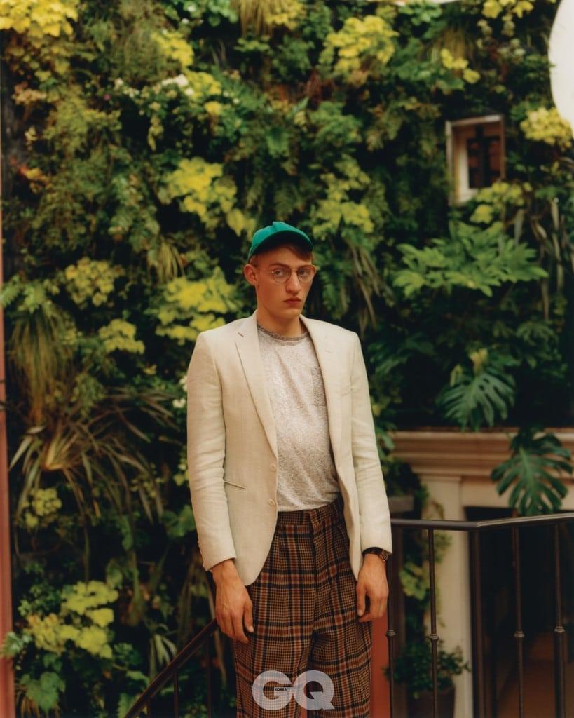 베이지 재킷 €830, 회색 티셔츠 €220, 모두 보스. 체크 팬츠 €450, 아미. 청록색 캡 €90, 아크네 스튜디오. 안경 €185, 에트니아 바르셀로나. 가죽 밴드 시계 €15000, 까르띠에.