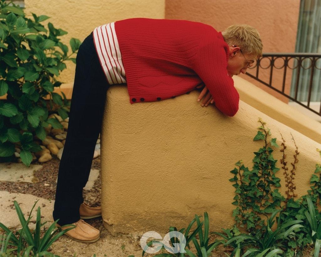 빨간 카디건과 남색 팬츠 가격 미정, 모두 프라다. 줄무늬 티셔츠 €35, 리바이스. 뿔테 안경 €185, 에트니아 바르셀로나. 스웨이드 슈즈 €150, 클락스.