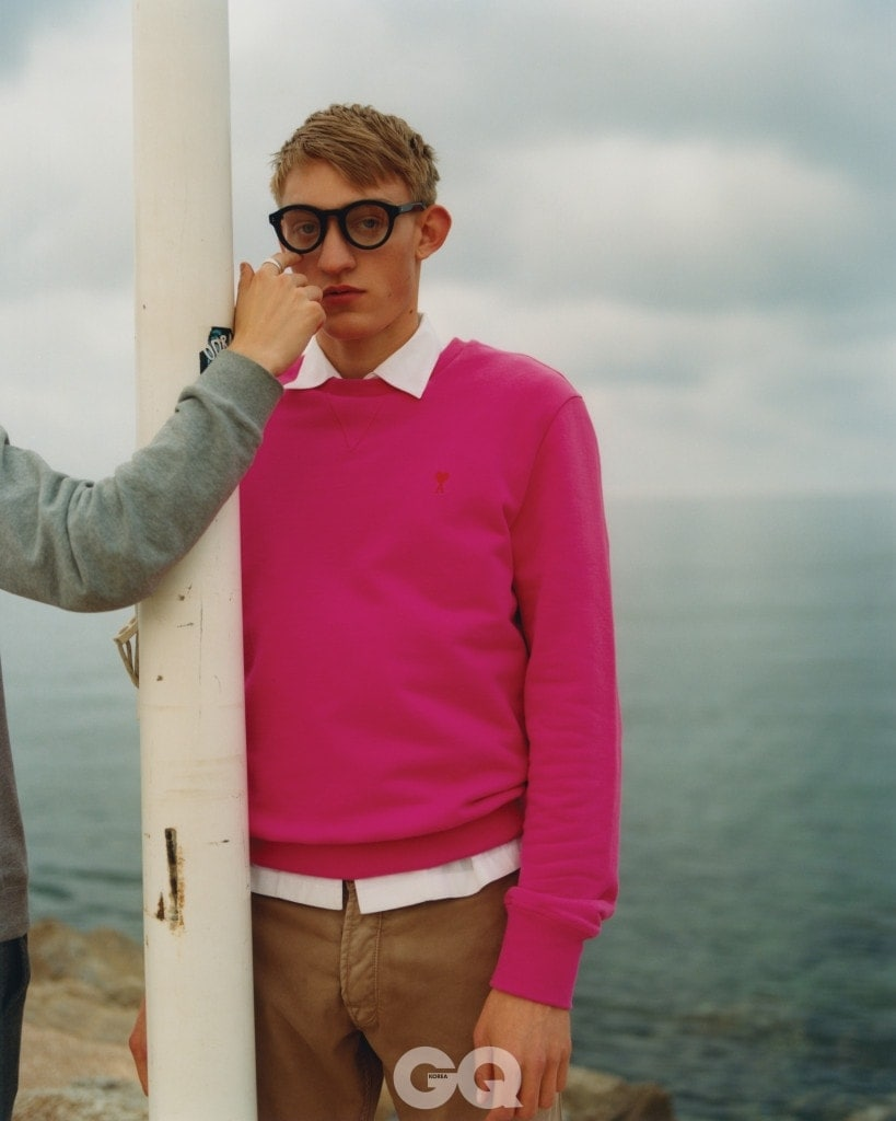 핑크색 니트 €160, 아미. 화이트 셔츠 €465, 스텔라 맥카트니. 치노 팬츠 €332, 마크 제이콥스. 뿔테 안경 €265, 모스콧.