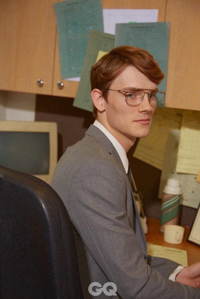 회색 수트, 화이트 셔츠, 회색 타이, 모두 타이거 오브 스웨덴. 금테 안경, 프라다 at 데이비드 클루로우.