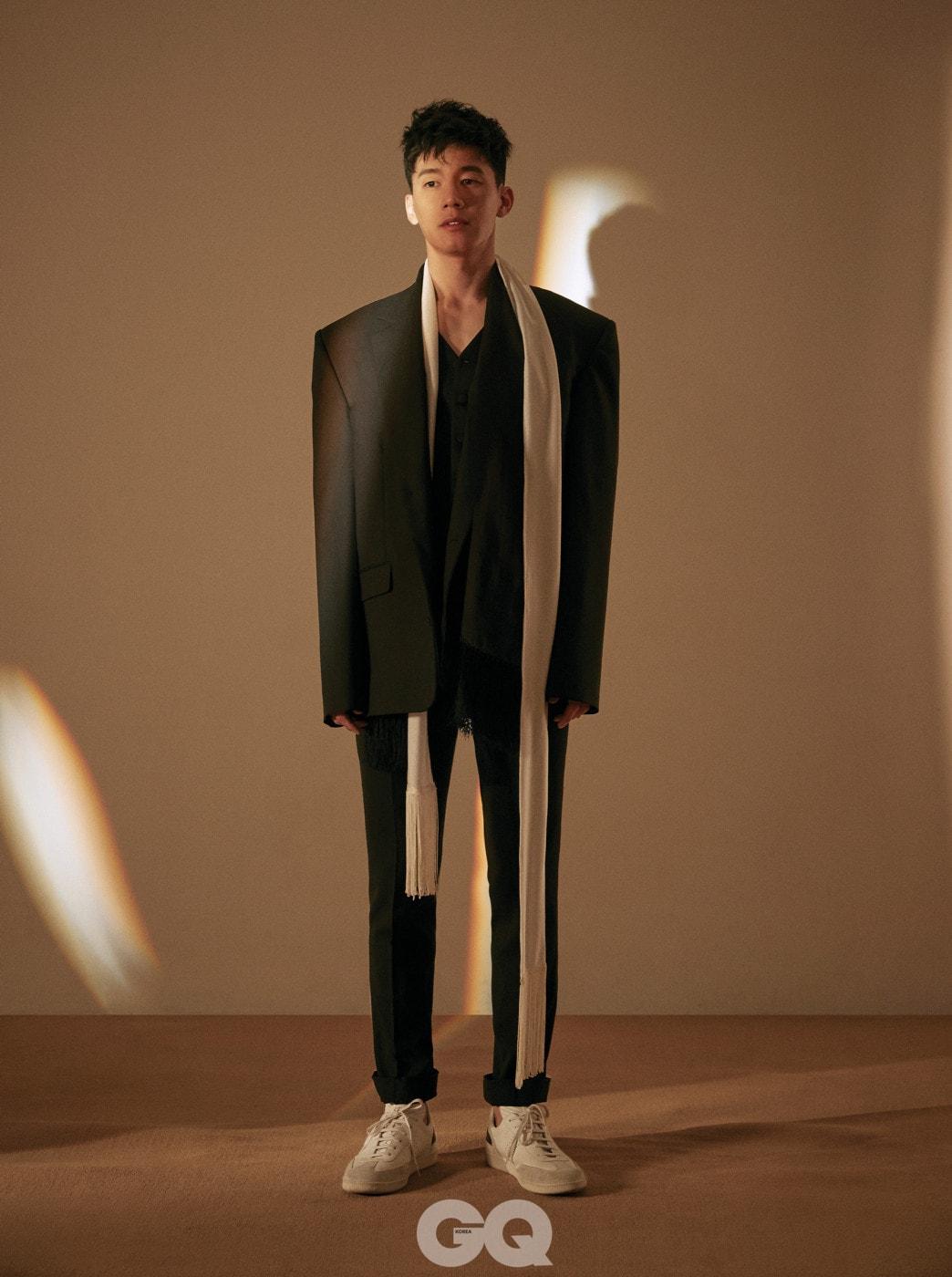 오버사이즈 블랙 재킷은 마틴 로즈 at 10 꼬르소꼬모. 블랙 베스트, 블랙 스카프 모두 돌체 & 가바나. 화이트 스니커즈, 디올 옴므. 블랙 팬츠, 화이트 스카프는 스타일리스트의 것.
