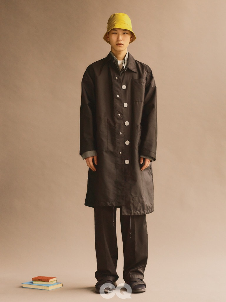 나일론 코트와 팬츠, 회색 셔츠와 티셔츠, 레인 햇과 샌들, 모두 프라다.
