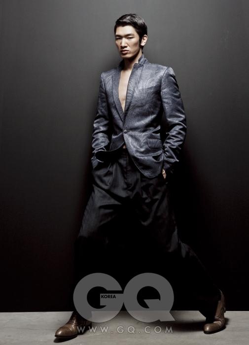 셔츠 없이 입은 재킷과 허리에 주름 장식이 있는 폭 넓은 팬츠, 밤색 구두 모두 루이 비통 2009 F/W 컬렉션.