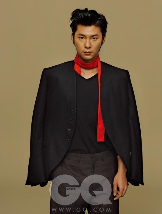Louis Vuitton 칼라 없는 남색 재킷과 갈색 팬츠, 브이넥 니트와 오렌지와 빨강이 섞인 머플러, 모두 루이 비통.