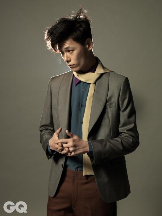 숄칼라 재킷, 보라색 칼라의 실크 셔츠, 갈색 팬츠, 미색 실크 스카프, 모두 프라다.