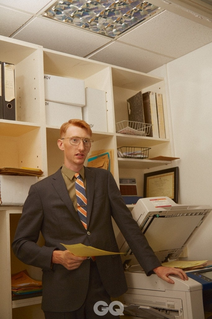 회색 수트, 꼬르넬리아니. 카키색 셔츠, H&M. 줄무늬 타이, 브룩스 브라더스. 타이바, 타테오시안. 금테 안경, 프라다 at 데이비드 클루로우.
