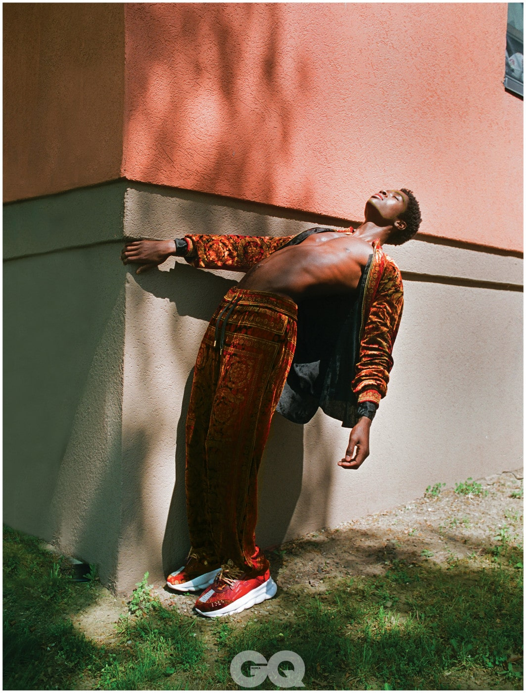 벨벳 재킷과 팬츠, 운동화, 모두 베르사체. 블랙 셔츠,  생 로랑 by 안토니 바카렐로.